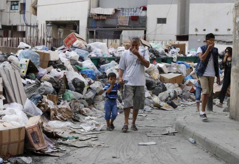 I residenti si coprono il naso mentre camminano passato immondizia accatastati lungo una strada a Beirut, Libano