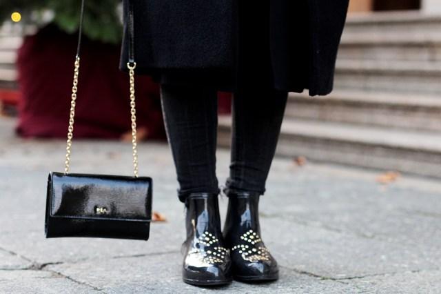 Bloggerin Helena zeigt schwarze Gummistiefel mit Nieten und elegante Tasche. Deutscher Modeblog aus Frankfurt.