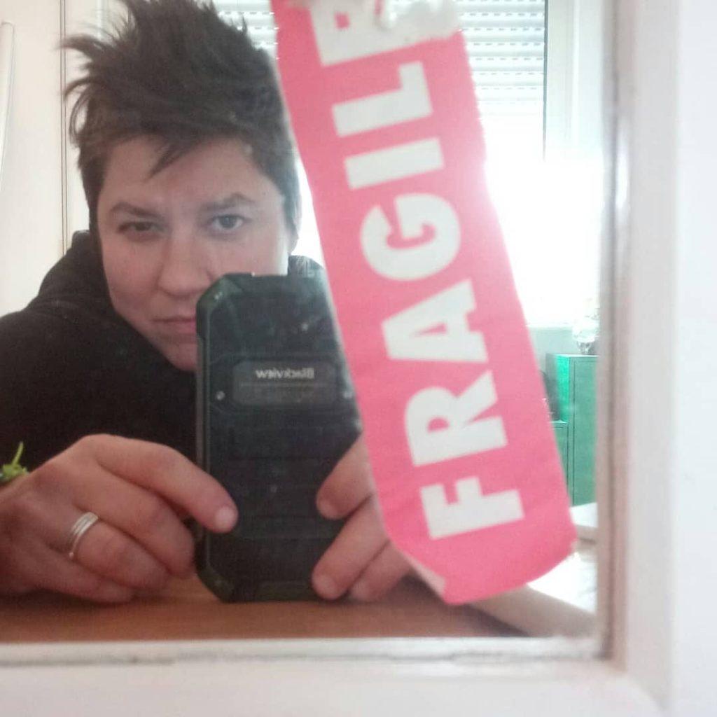 """une photo de miroir avec un reflet d'une personne et une étiquette """"fragile"""" par dessus."""