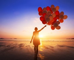 自由を手に入れる inspiration, joy and happiness concept, silhouette of woman with many flying balloons on the beach