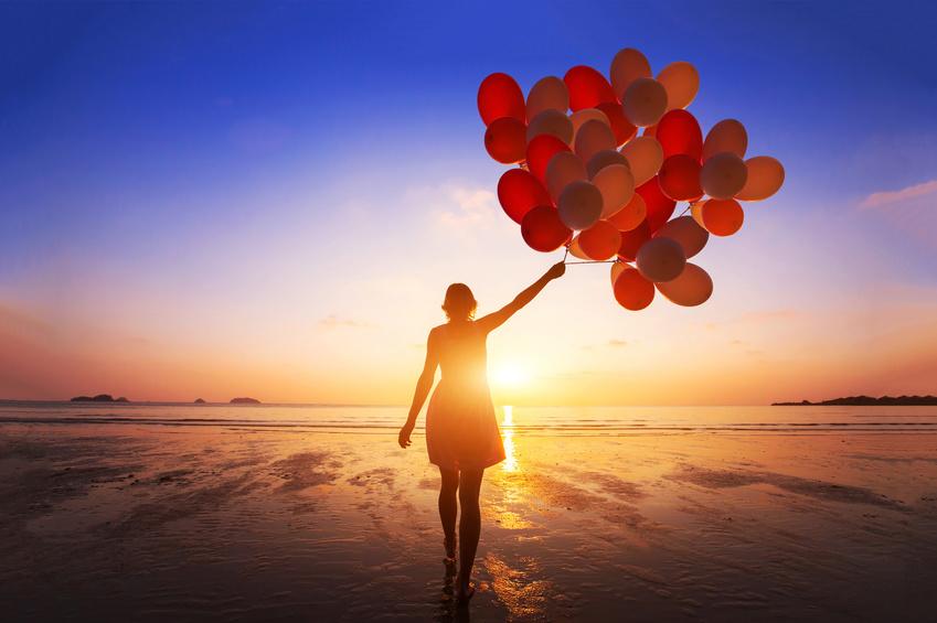 自由を手に入れる inspiration, joy and happiness concept, silhouette of woman with many flying balloons on the beach