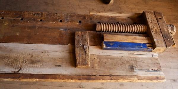 Deltalj som viser undersida. Legg merke til klossen som fester høvelbenkskuffa. Bordet som dannar høvelbenkskuffa er justert med høvel, men elles er det skuroverflate etter oppgangssag vi ser. Undersida av planken som dannar kjernen i høvelbenkplata er høvla slett på undersida. Truleg har denne planken vore planhøvla og dimensjonert i samband med at benken vart laga. Foto: Roald Renmælmo