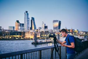 Young man photographing with tripod on embankment against urban skyline