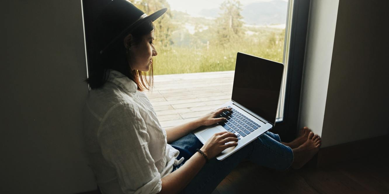 Young woman in hat browsing laptop, shopping or working online from home