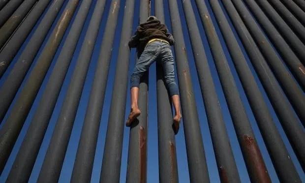 USA IMMIGRATION CARAVAN migrant climbs border fence