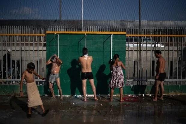 IMMIGRATION CARAVAN migrants shower at shelter in Tijuana