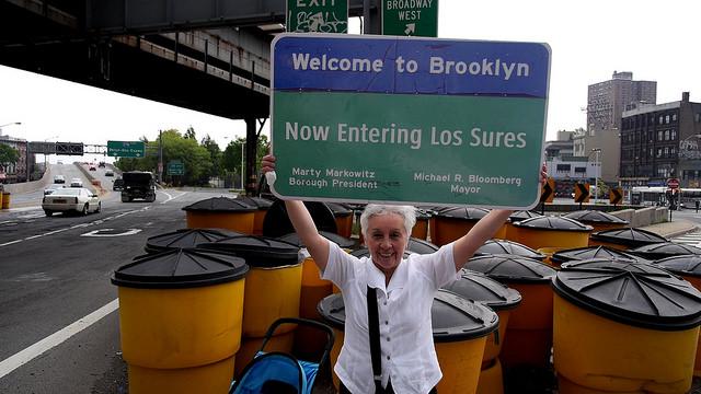 Marta with Now Entering Los Sures Sign. Credit: Christopher Allen