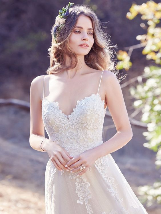 Maggie Sottero - EMILY, Chic and boho-inspired, this A-line features horizontal lace motifs, scattered lace appliqués, and a striking lace hem on tulle over dot tulle. Spaghetti straps run from sweetheart neckline to square back trimmed with illusion lace. Finished with covered buttons over zipper closure.