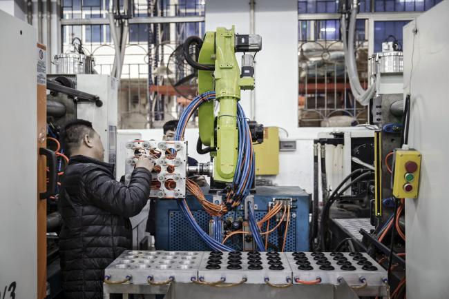 © Bloomberg. A technician adjusts an industrial robot manufactured by the E-Deodar Robot Equipment Co., a wholly-owned subsidiary of Ningbo Techmation Co., as it stands on the production line of Guangdong Shiyi Furniture Co. in Foshan, China, on Tuesday, Feb. 28, 2017. Photographer: Qilai Shen/Bloomberg