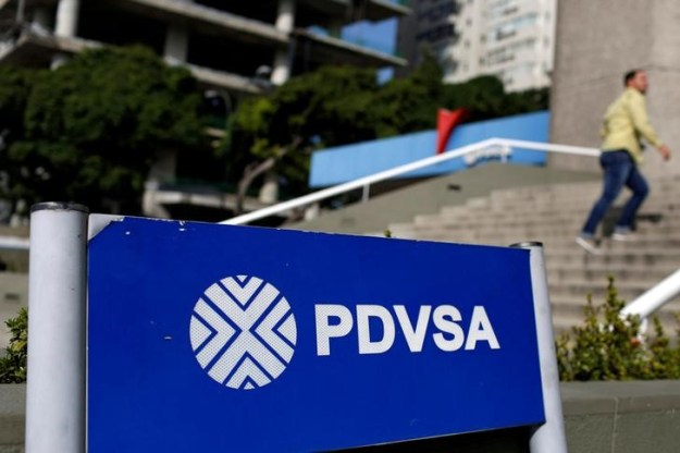 © Reuters. FILE PHOTO: A man walks past a gas station with the logos of the Venezuelan state oil company PDVSA in Caracas