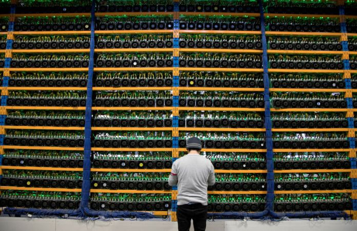 © Reuters. FILE PHOTO: A worker checks the fans on miners at the cryptocurrency farming operation Bitfarms in Farnham Quebec
