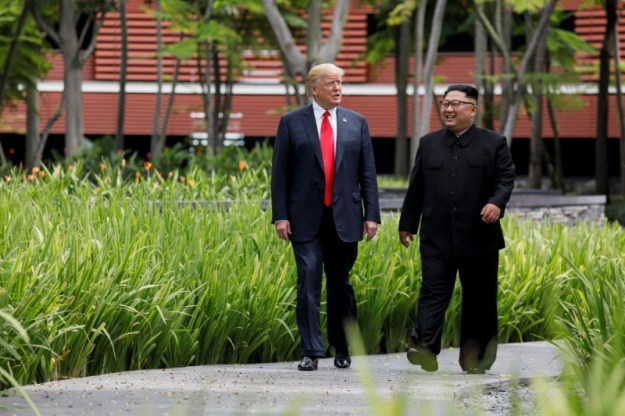 © Reuters. U.S. President Trump and North Korea's Kim walk together before their working lunch during their summit in Singapore