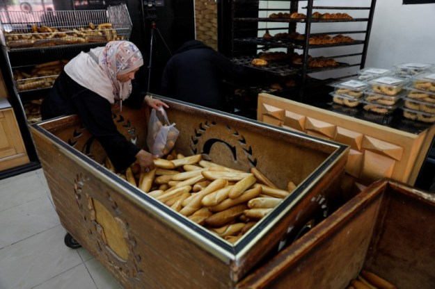 © Reuters. A woman picks up bread in a shop in Tripoli