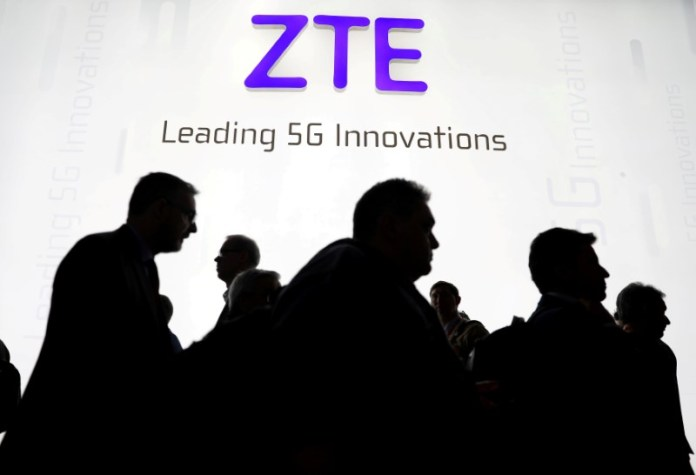 © Reuters. FILE PHOTO: Visitors pass in front of the ZTE booth at the Mobile World Congress in Barcelona