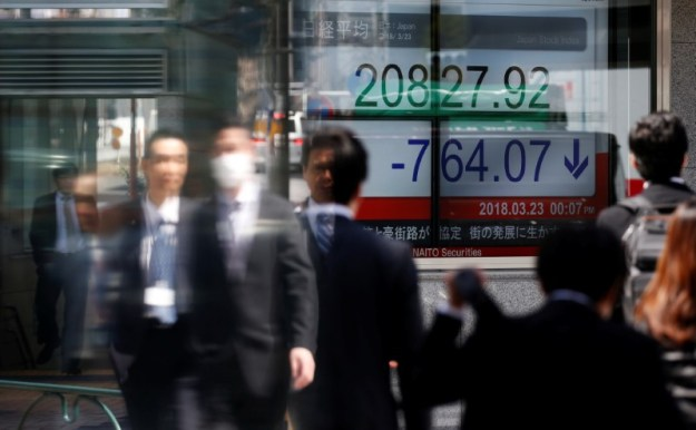 © Reuters. People walk past an electronic board showing Japan's Nikkei average outside a brokerage in Tokyo