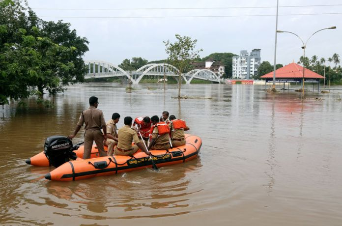 © Reuters. Rescue personnel patrol the flooded waters on the banks of Periyar River after the opening of Idamalayar and Cheruthoni dam shutters following heavy rains, on the outskirts of Kochi