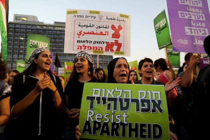 © Reuters. Israeli Arabs and their supporters take part in a rally to protest against Jewish nation-state law in Rabin square in Tel Aviv