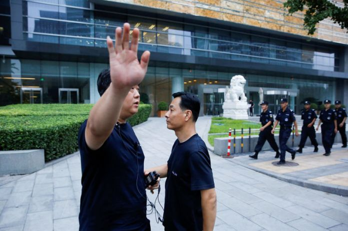 © Reuters. FILE PHOTO: A police officer gestures at the photographer as security patrol outside the headquarters of China's banking regulator in Beijing