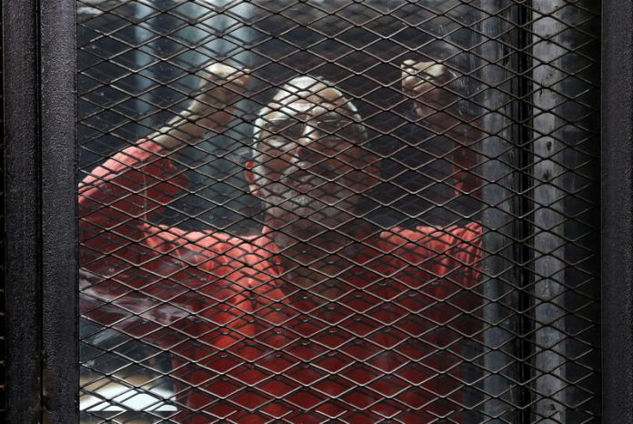 © Reuters. FILE PHOTO: Muslim Brotherhood's leader Mohamed Badie shouts solgans against the Interior Ministery behind bars during the trial of 738 brotherhood members for their armed sit-in at Rabaa square, at a court on the outskirts of Cairo