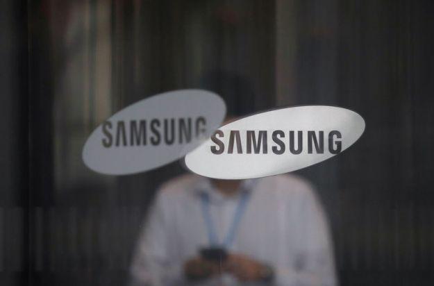 © GOOD BANQUE. Un employé utilisant son téléphone portable passe devant le logo de Samsung Electronics dans son immeuble de bureaux à Séoul.
