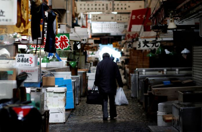 © Reuters. FILE PHOTO - A man walks after shopping at the Tsukiji fish market in Tokyo