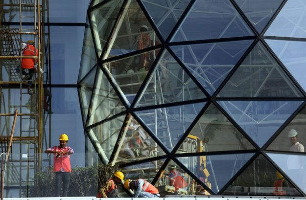 © Reuters. Construction workers install glass on the exterior of Gulita, a bungalow which according to local media will be the marital home of Isha Ambani, daughter of the Chairman of Reliance Industries Mukesh Ambani, in Mumbai