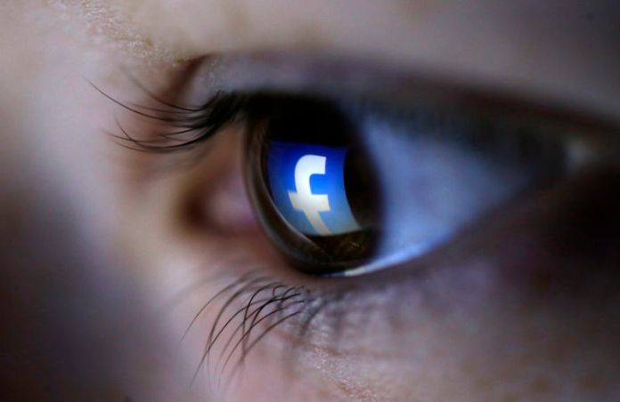 © Reuters. A picture illustration shows a Facebook logo reflected in a person's eye, in Zenica
