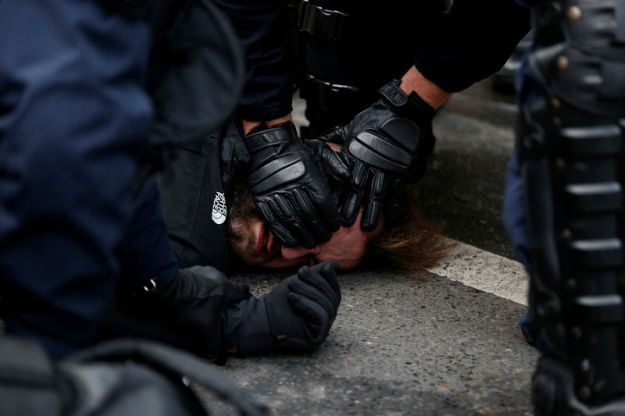 © Reuters. French CRS riot police apprehend a man in a street near Saint Lazare train station during a national day of protest by the