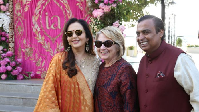 © Reuters. Former US Secretary of State Hillary Clinton poses with Mukesh Ambani, Chairman of Reliance Industries, and his wife Nita Ambani after her arrival in Udaipur