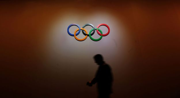 © Reuters. A man walks past the Olympic Rings as he walks out of the 133rd IOC session in Buenos Aires