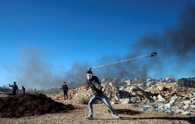 © Reuters. Palestinian uses a sling to hurl stones during clashes with Israeli troops near the Jewish settlement of Beit El, near Ramallah, in the Israeli-occupied West Bank