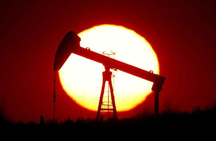 © Reuters. FILE PHOTO: The sun sets behind a pump cylinder outside Saint-Fiacre