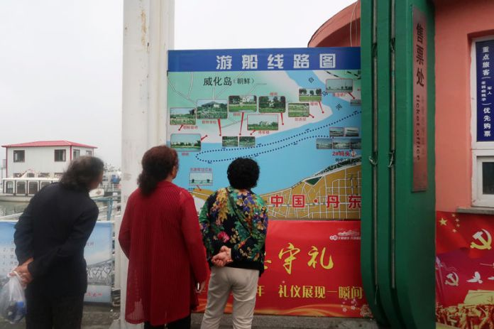 © Reuters. Chinese tourists look at a map detailing the route of a boat tour on the Yalu River, which separates North Korea and China, at a ticket office in Dandong