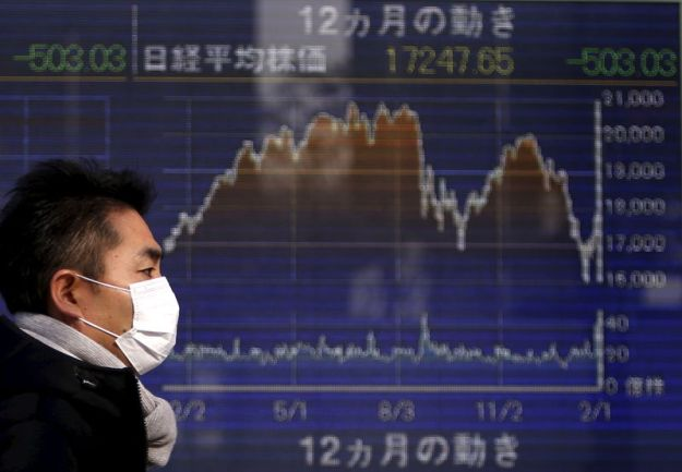 © Reuters. FILE PHOTO: A pedestrian walks past an electronic board showing the graph of the recent fluctuations of Japan's Nikkei average outside a brokerage in Tokyo