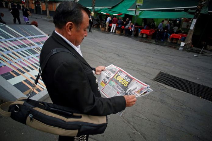 © Reuters. A mariachi musician reads a newspaper near a crime scene on the edge of Plaza Garibaldi in Mexico City