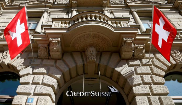 © Reuters. FILE PHOTO: Switzerland's national flags fly beside the logo of Swiss bank Credit Suisse in Zurich