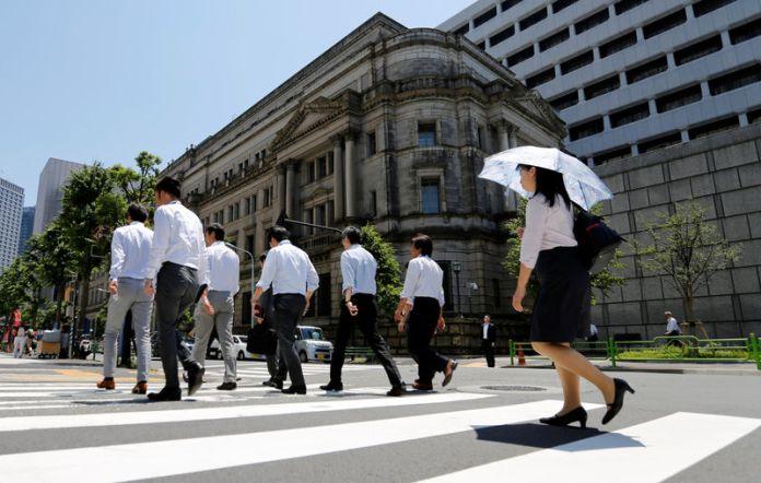 © Reuters. People walk past the Bank of Japan building in Tokyo