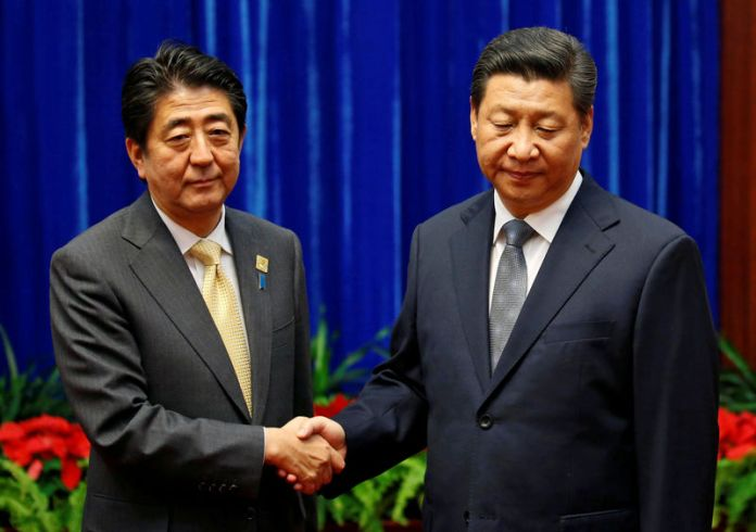 © Reuters. FILE PHOTO: China's President Xi Jinping shakes hands with Japan's Prime Minister Shinzo Abe during their meeting on the sidelines of the APEC meetings in Beijing