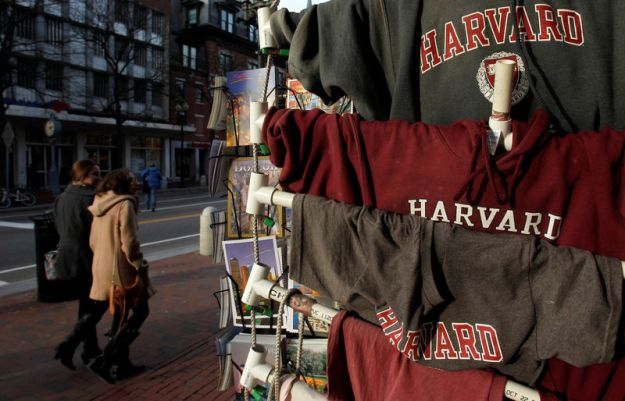 © Reuters. FILE PHOTO: People walk past Harvard University t-shirts for sale in Harvard Square in Cambridge