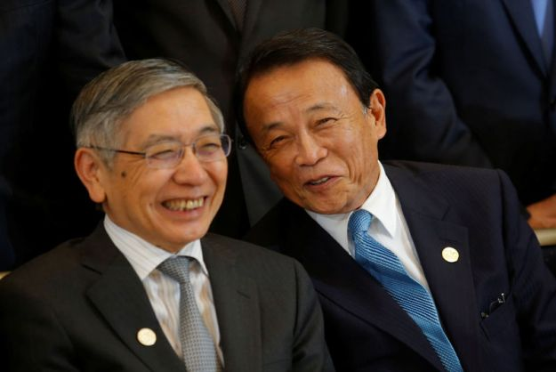 © Reuters. Japan's Finance Minister Taro Aso talks to Governor of the Bank of Japan Haruhiko Kuroda during G20 finance minsters and bank governors photo session at International Monetary Fund - World Bank Annual Meeting 2018 in Nusa Dua