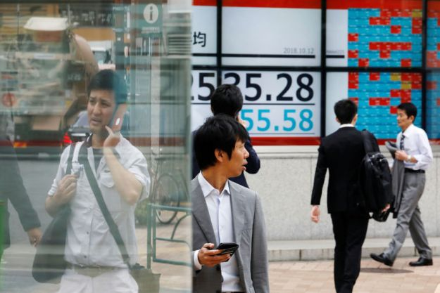 © Reuters. FILE PHOTO - People walk past an electronic board showing Japan's Nikkei average outside a brokerage in Tokyo