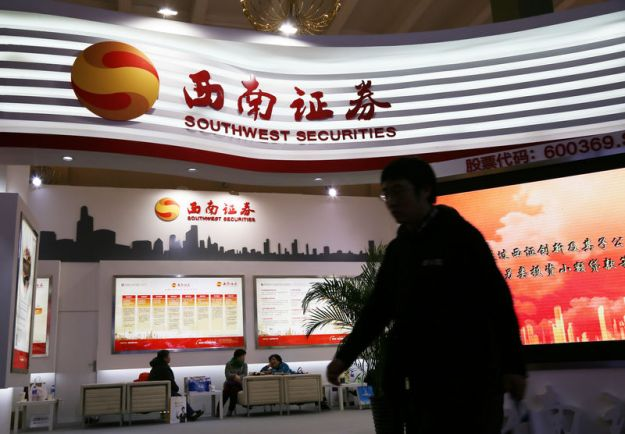 © Reuters. Man walks past a booth of Southwest Securities at a finance expo in Beijing