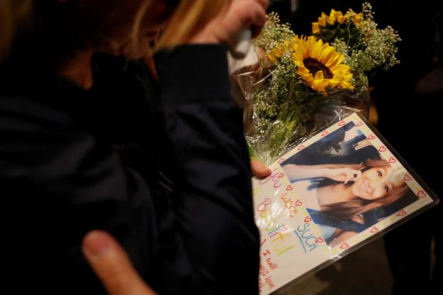 © Reuters. A mourner arrives with a picture of one of her friends at a vigil for the victims of the mass shooting in Thousand Oaks