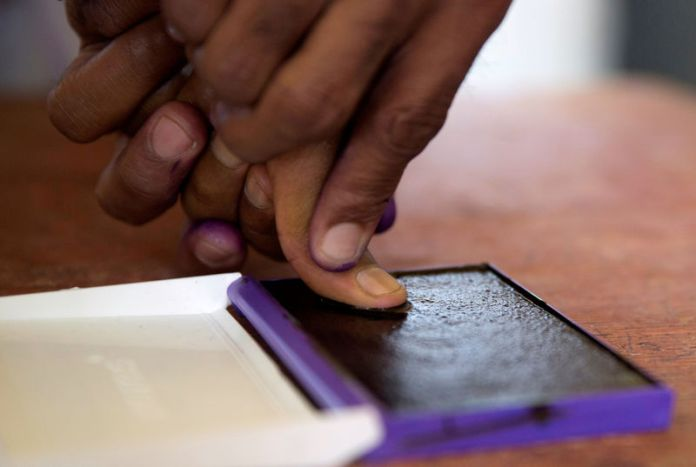 © Reuters. FILE PHOTO: An electoral commission official marks with ink the thumb of a voter after casting his ballot during the presidential election at a polling centre in Analakely, Antananarivo