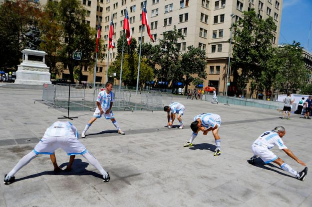 © Reuters. FILE PHOTO: Argentinian players warm-up before their soccer match against Chile during 12th Homeless World Cup in Santiago City October 19, 2014