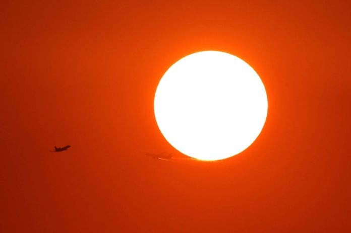 © Reuters. Two planes fly in front of the setting sun in Shanghai