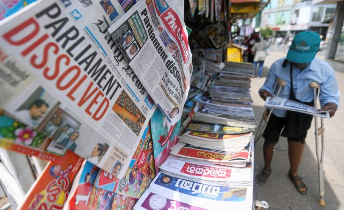 © Reuters. A man reads a newspaper at stall carrying the news of the Sri Lanka's parliament being dissolved, on a main road in Colombo,