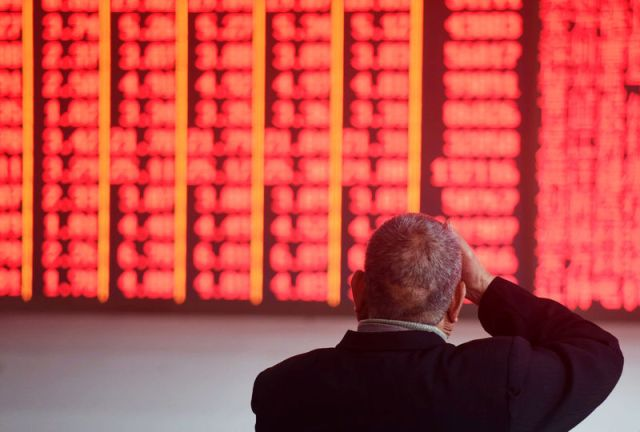 © Reuters. Man sits in front of an electronic board showing stock information at a brokerage house in Hangzhou