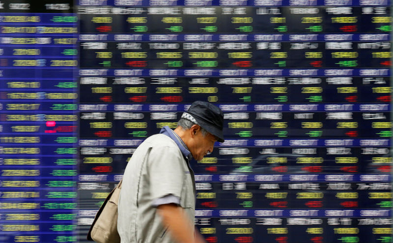 © Reuters. A man walks past an electronic stock quotation board outside a brokerage in Tokyo