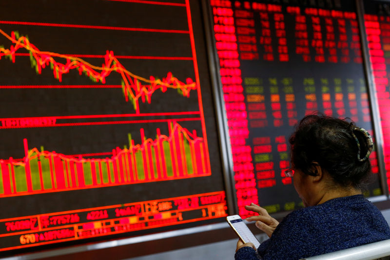 © Reuters. An investor sits in front of a board showing stock information at a brokerage office in Beijing